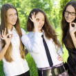 Stock Photo: Three happy student girl give sign okey in park