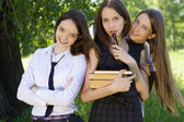 Three beautiful student girl with books in the park — Stock Photo