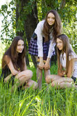 Three beautiful student girls with books in the park — Stockfoto