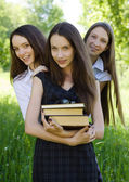 Three happy student girl with books in the park — Stock Photo