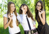 Three happy student girl give the sign okey in the park — Stock Photo