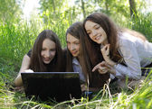 Three students relax and laughing on the grass in the park — Stock Photo