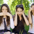 Three beautiful student girls spend time in the park - Stock Photo