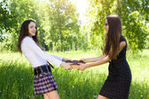 Two student girl taken one same book outdoor — Stock Photo