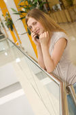 Young woman speaking on cellphone in shopping centre — Stockfoto
