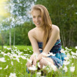 Pretty teen girl on the field with snowdrops — Stock Photo