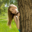 Beautiful teen girl look out from the tree in the park — Stock Photo
