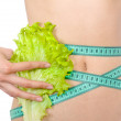 Tape measure and leaf of lettuce on the waist isolated — Stock Photo
