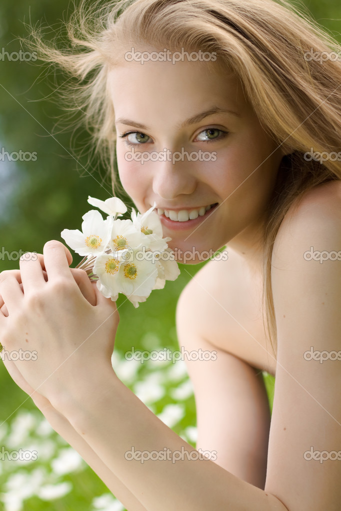 Portrait of beautiful teen girl with white flowers in the park - Stock