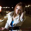 Beautiful young woman standing on illuminated street at night — Stock Photo #3752022