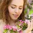 Beautiful woman in blossom orchard sunshine - Stock Photo