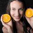 Portrait of girl with two halfs of orange in water studio — Stock Photo