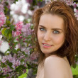 Portrait of beautiful woman in blossom orchard — Stock Photo