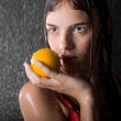 Portrait of pretty teen with orange in water studio — Stock Photo