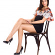 Sexy brunette in mini seat on chair — Stock Photo