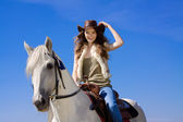 Young cowgirl on white horse smile — Stock Photo