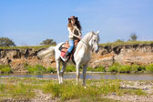 Young cowgirl on white horse at the river — Stock Photo