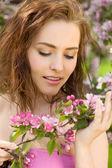 Beautiful woman in blossom orchard sunshine — Stock Photo