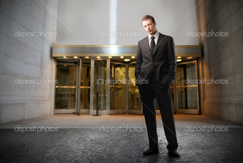 Young businessman standing in front of an office building — Stock Photo #3121784