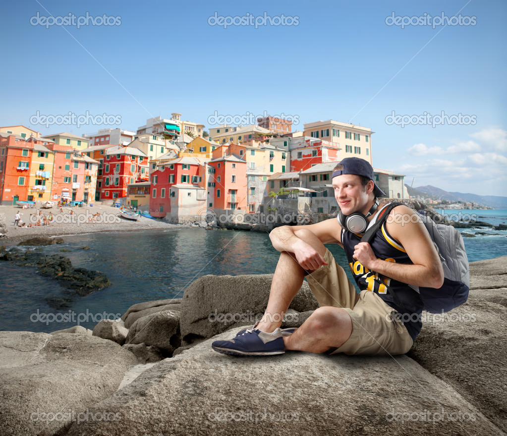 Young man sittin gon the rocks in front of a gulf with typical italian village on the background — Stock Photo #3121840