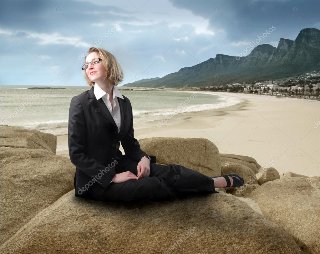 Smiling businesswoman sitting on a rock at the seaside — Stock Photo #3194405