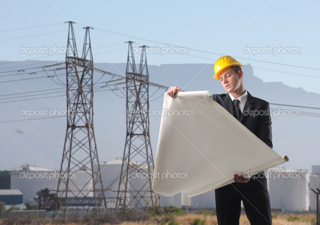 Young engineer observing a plan with industrial site on the background  Stock Photo #3194868