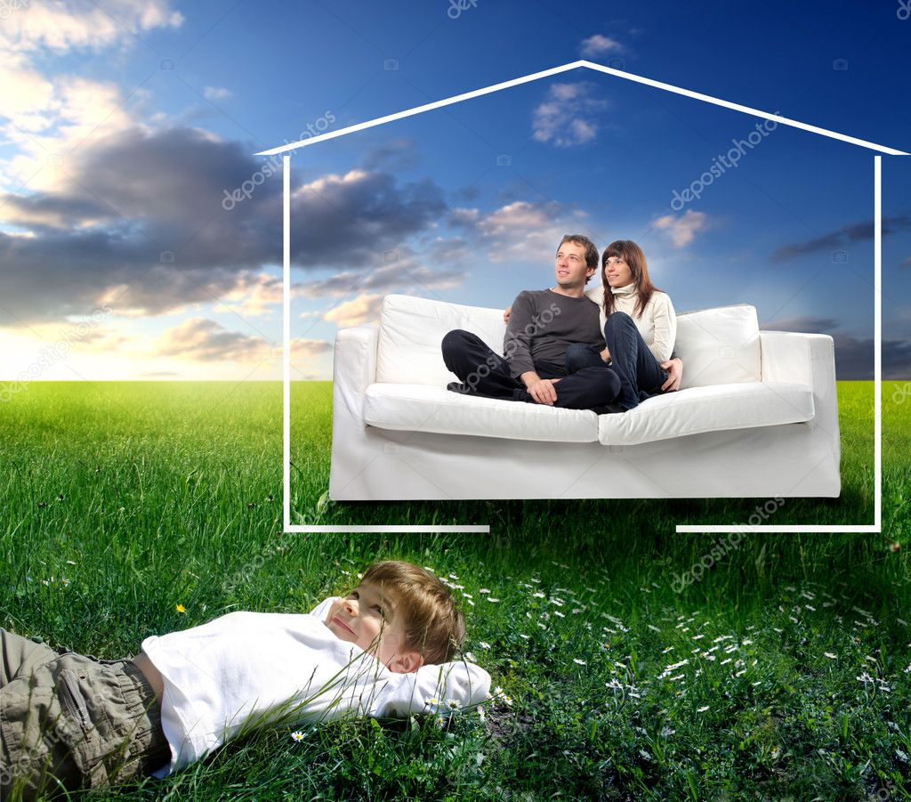 Young couple sitting on a sofa surrounded by the form of a house and smiling child lying on green meadow — Stock Photo #3195599