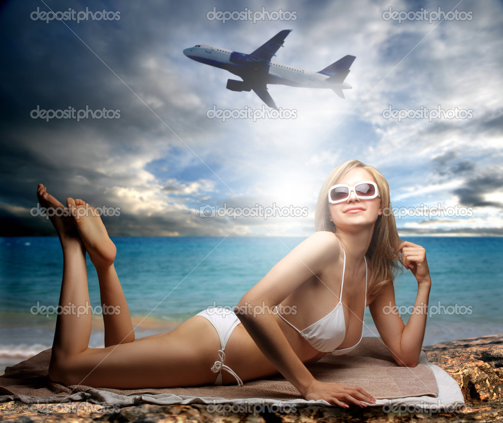 Beautiful woman in swimsuit lying on a beach with plane on the background — Photo #3195852