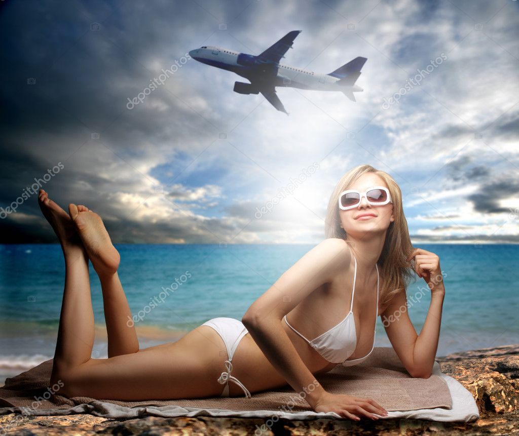Beautiful woman in swimsuit lying on a beach with plane on the background — Lizenzfreies Foto #3195852