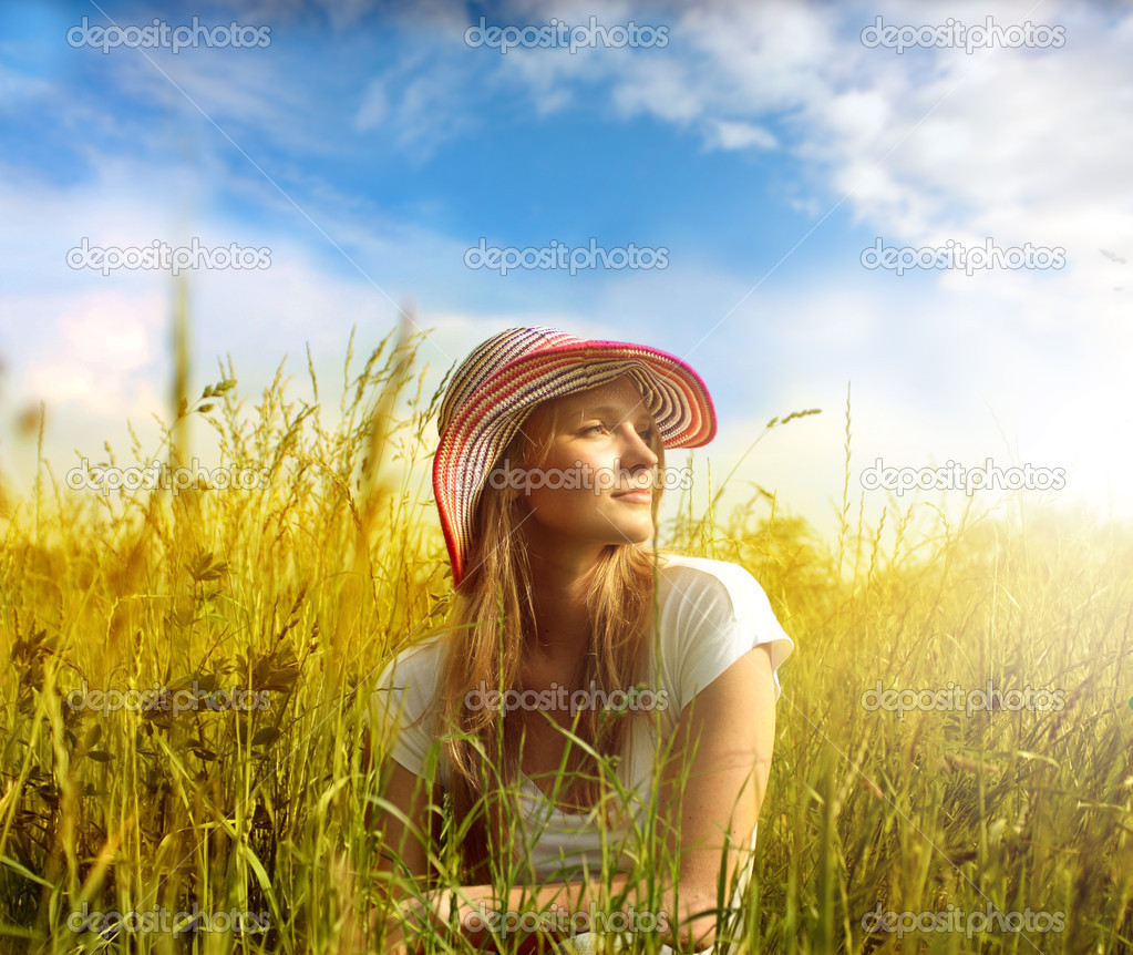 Beautiful woman sitting on a wheatfield — Stock Photo #3195974