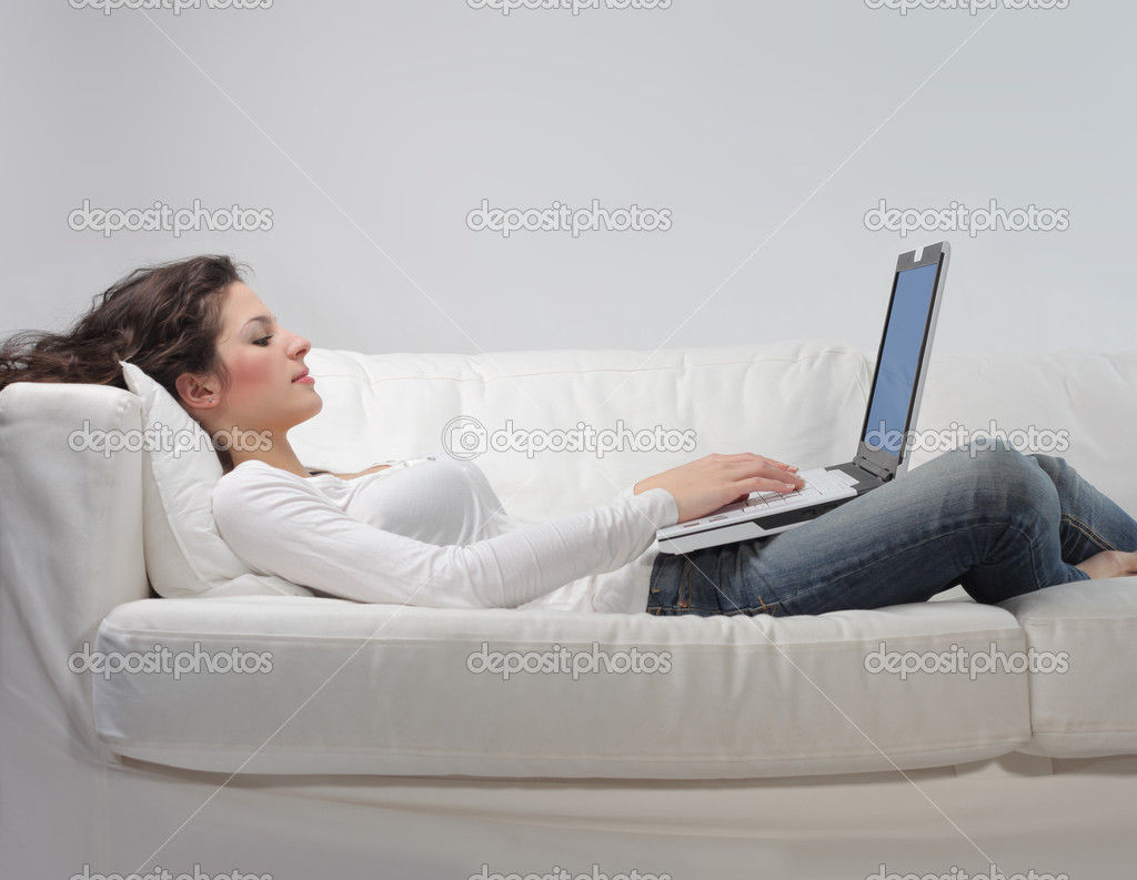 Young woman lying on a sofa and using a laptop — Stock Photo #3197121