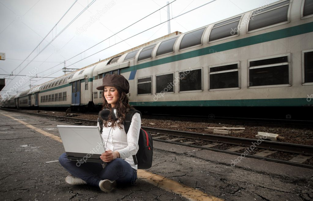 Young woman sitting on the platform of a train station and using a laptop — Stock Photo #3197129