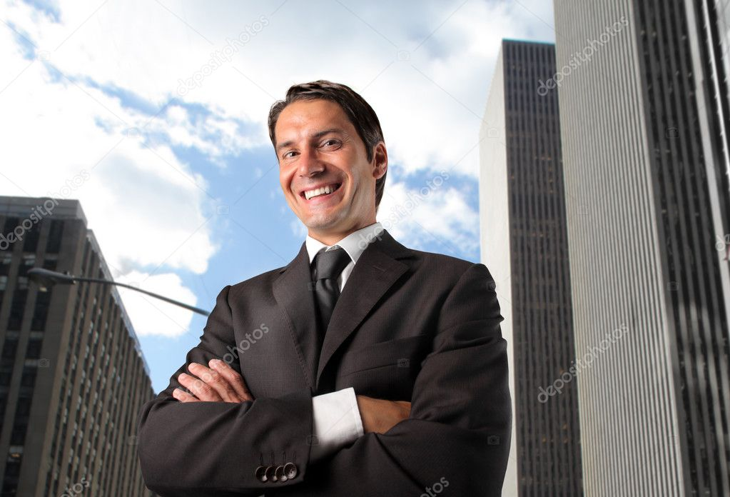 Smiling businessman with cityscape on the background — Stock Photo #3201017