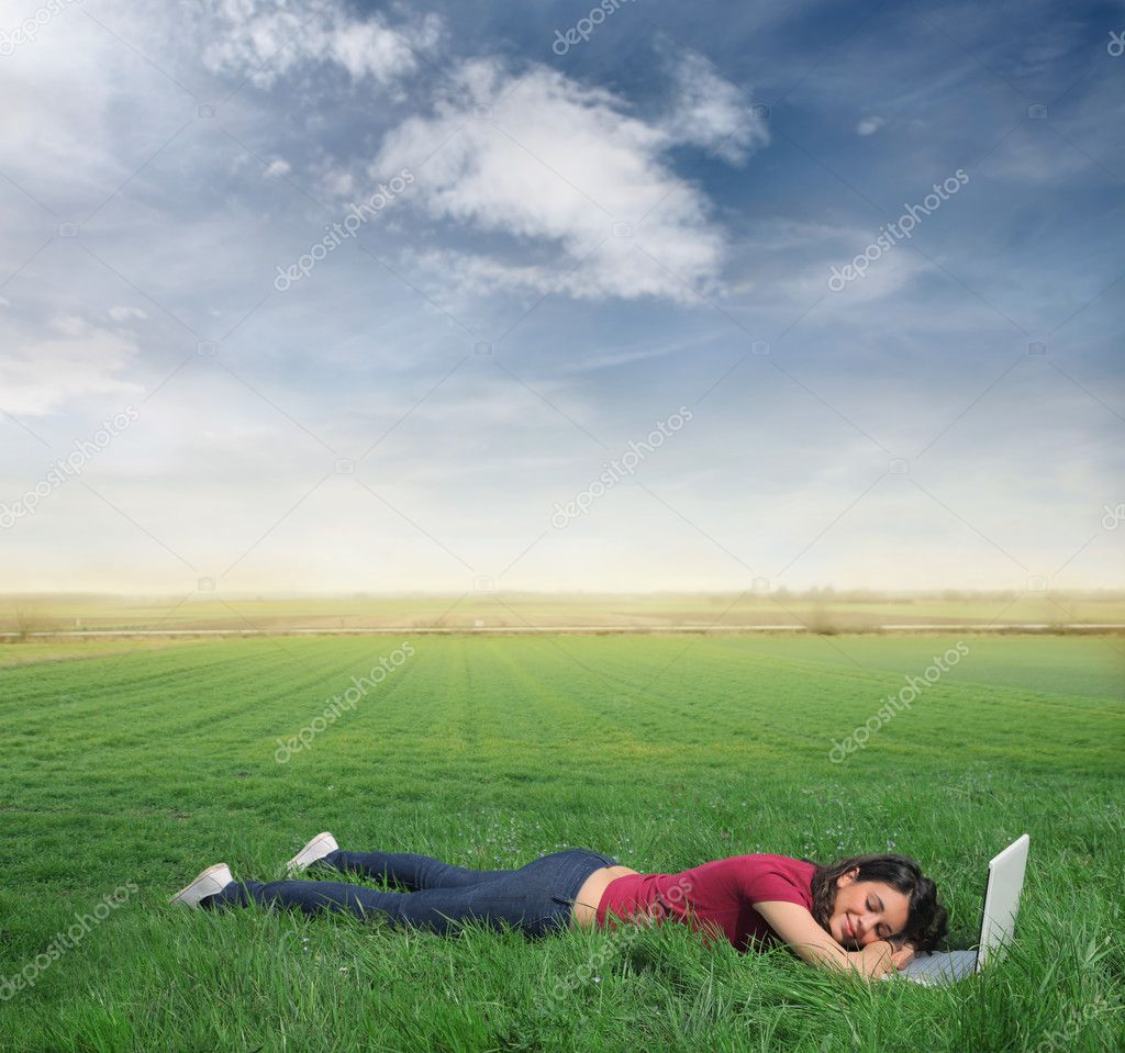 Young woman sleeping on a green meadow with a laptop in front of her — Stock Photo #3201883