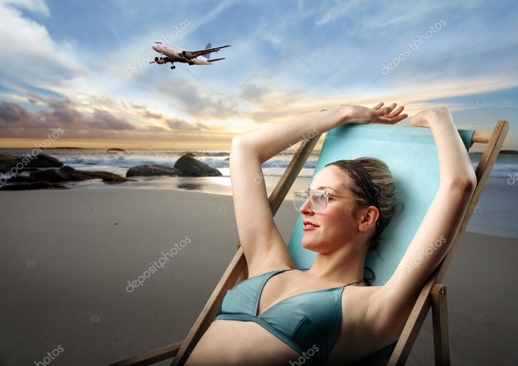 Young woman in swimsuit lying on a deckchair on a beach with airplane on the background — Stok fotoğraf #3202810