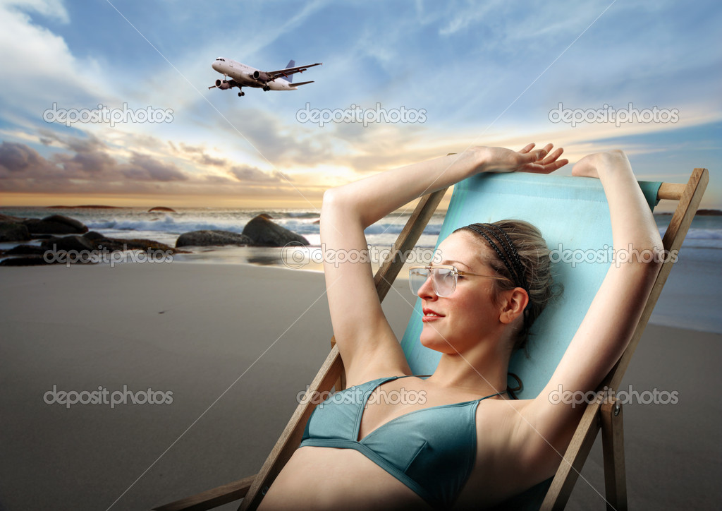 Young woman in swimsuit lying on a deckchair on a beach with airplane on the background — Photo #3202810
