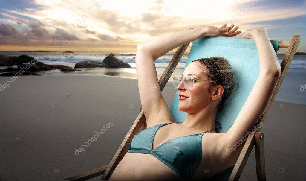 Beautiful woman in swimsuit lying on a deckchair — Stock Photo #3204046