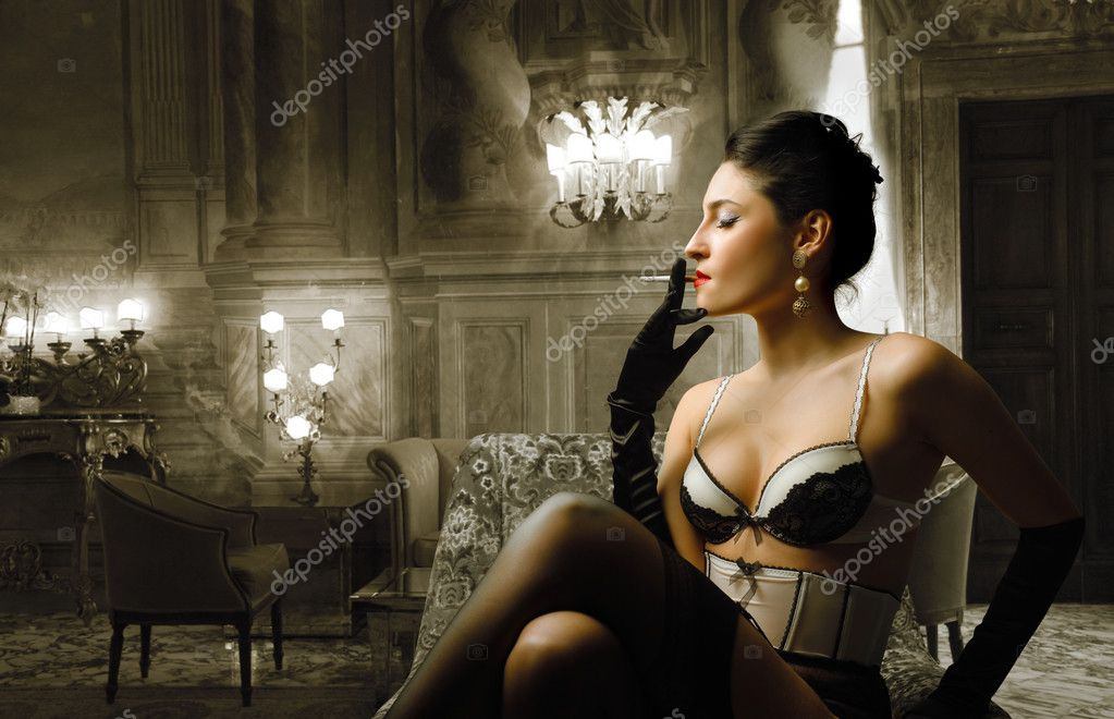 Beautiful woman in lingerie smoking a cigarette in a luxury hotel room — Stock Photo #3208103