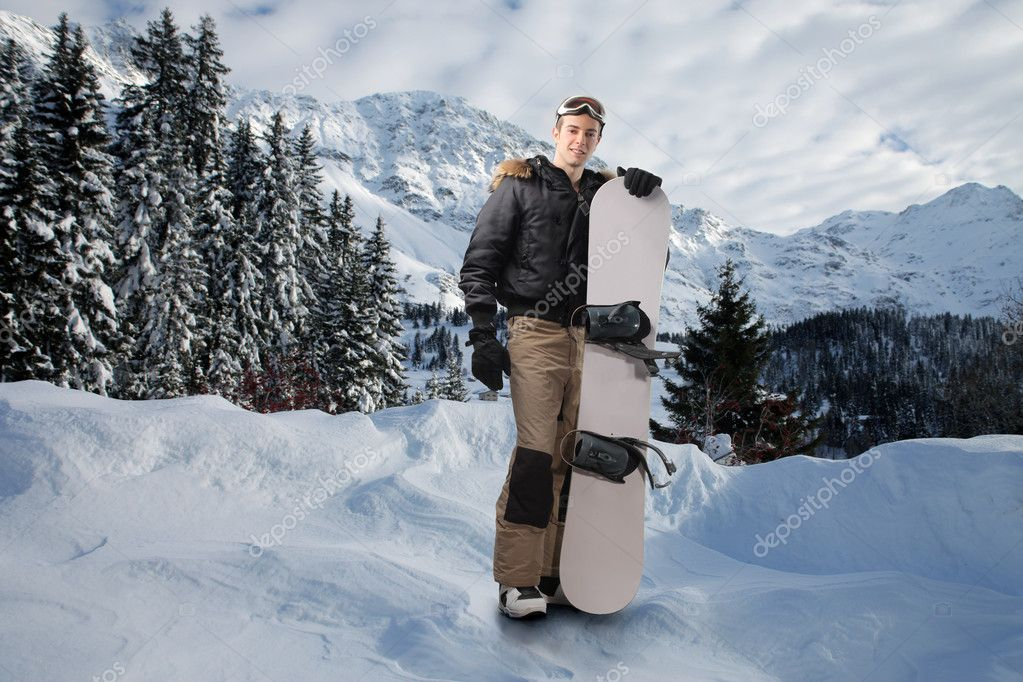 Young man carrying a snowboard at the mountain — Stock Photo #3208133