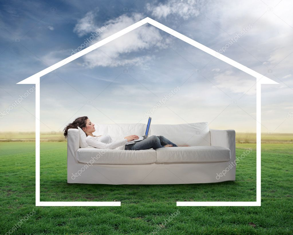 Young woman lying on a sofa on a green meadow using a laptop and surrounded by the form of a house — Stok fotoğraf #3208163