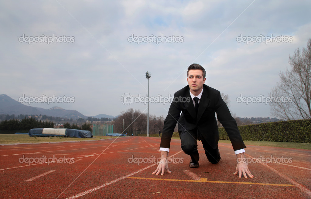 Businessman kneeling on the starting grid of a running track — Stock Photo #3208253