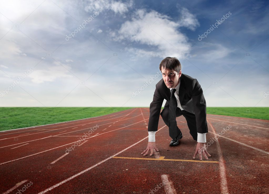 Businessman kneeling on the starting grid of a running track — ストック写真 #3208280