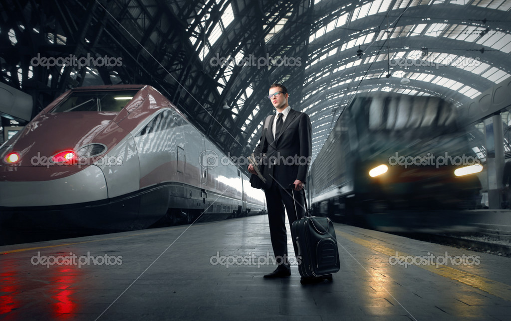 Businessman carrying a suitcase standing on the platform of a train station — Stok fotoğraf #3208291