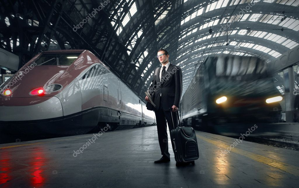 Businessman carrying a suitcase standing on the platform of a train station  Lizenzfreies Foto #3208291