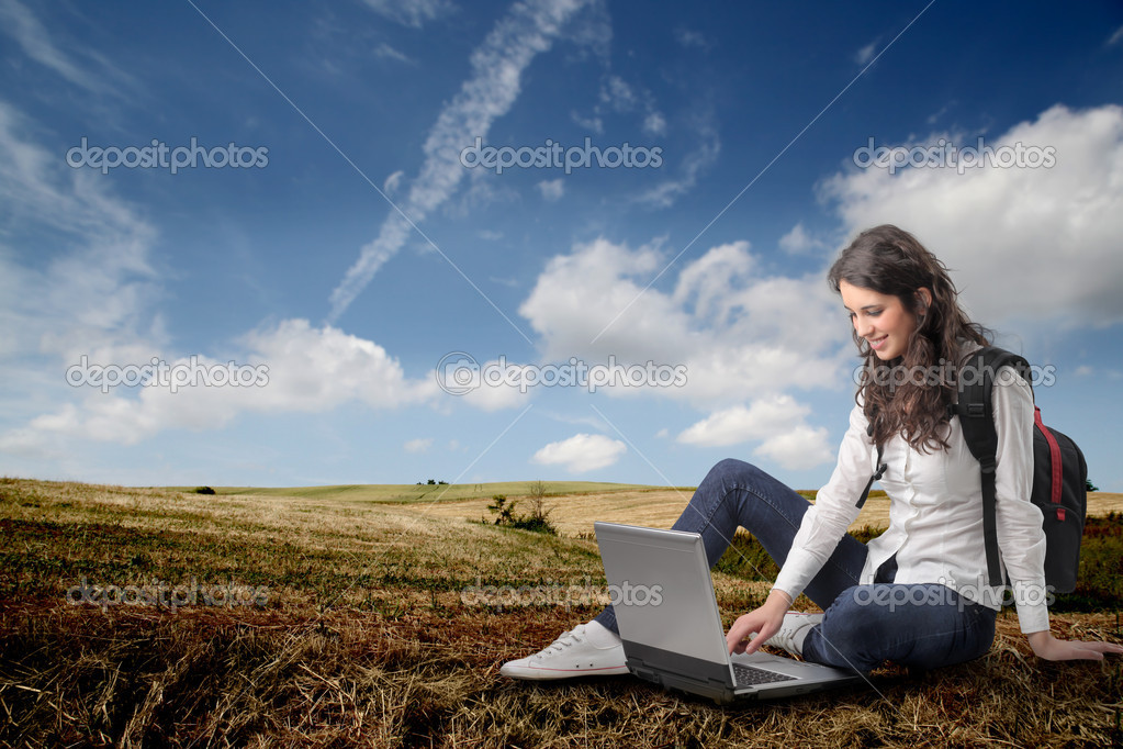 Young woman sitting on a field and using a laptop — Stock Photo #3208472