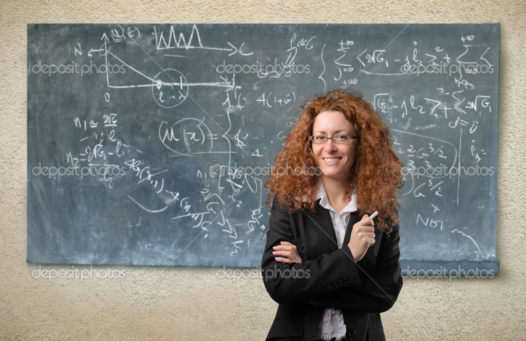 Smiling teacher standing in front of a blackboard — Stock Photo #3208781