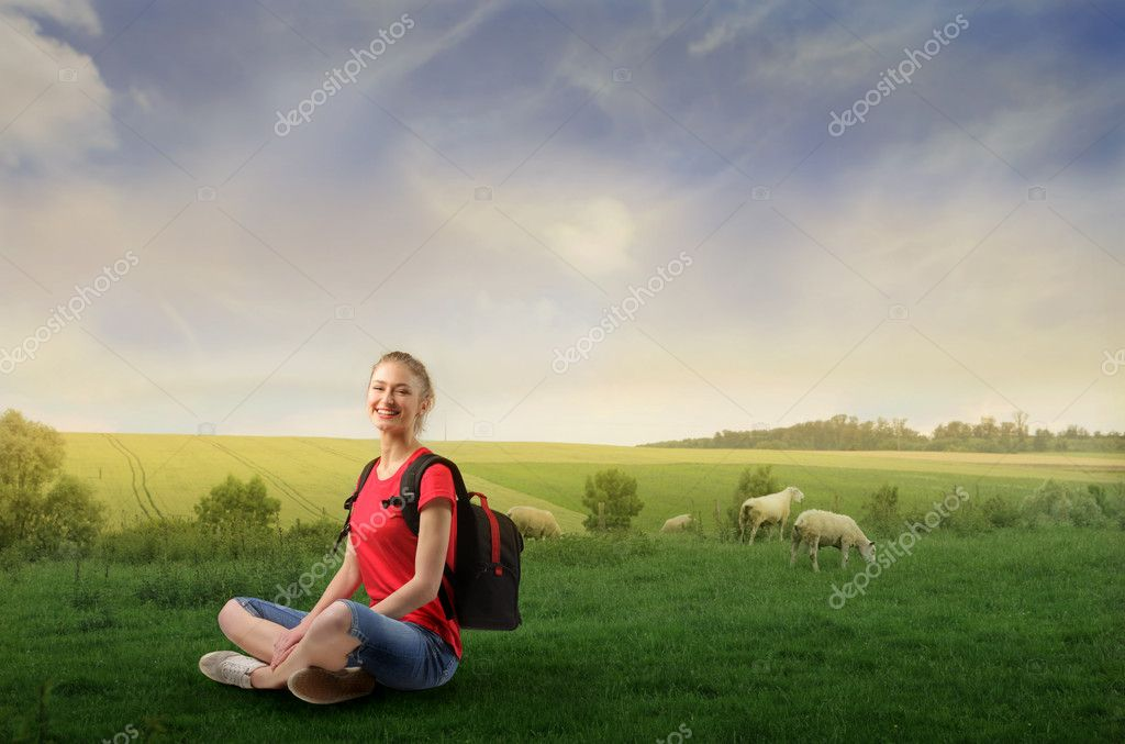 Smilin woman sitting on a green meadow with some animals on the background  Foto Stock #3209144
