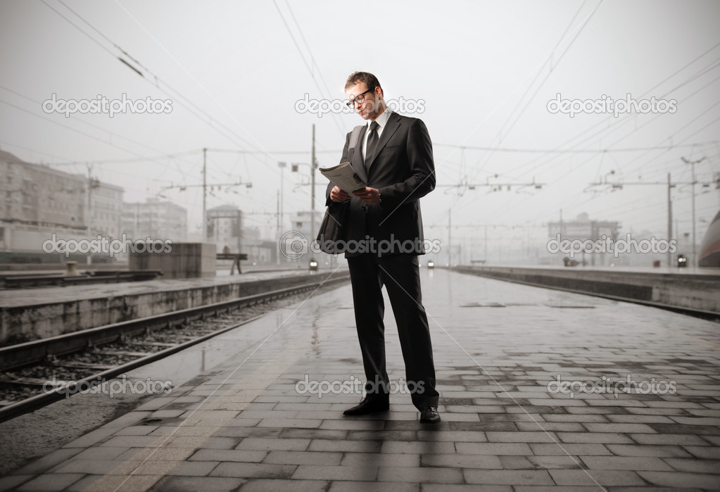 Businessman reading a newspaper standing on the platform of a train station — Stock Photo #3209785