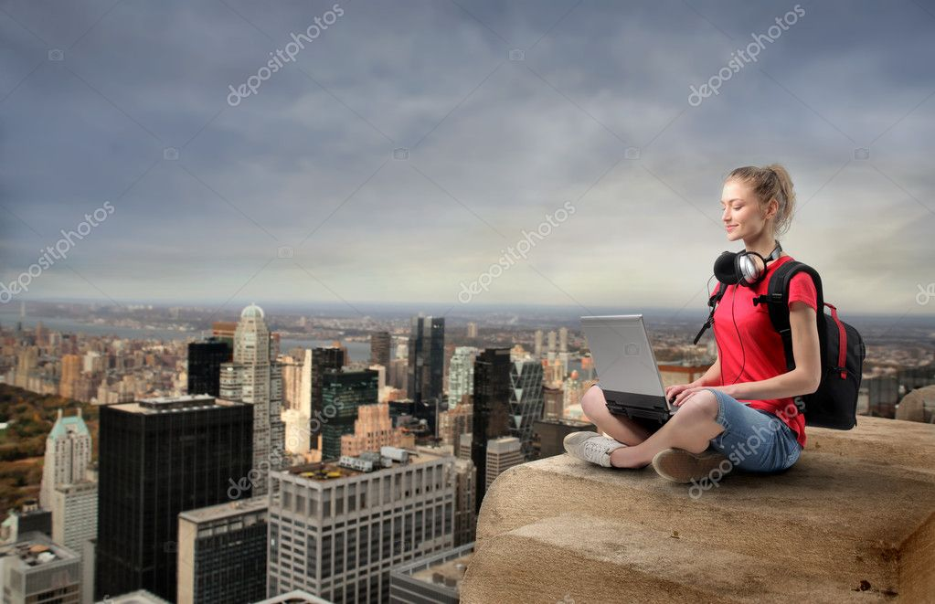 Young woman sitting on the top of a skyscraper and using a laptop — Stock Photo #3209956