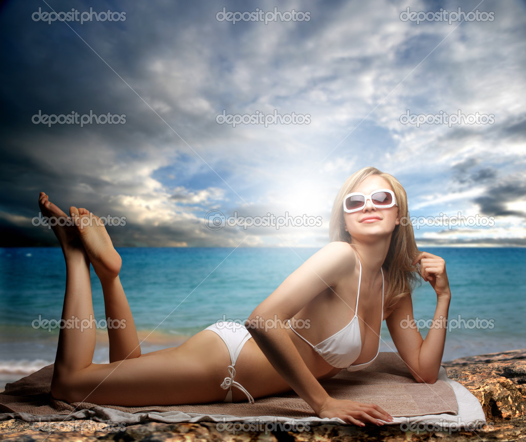 Beautiful woman in bikini laying on the beach — Stock Photo #3231959